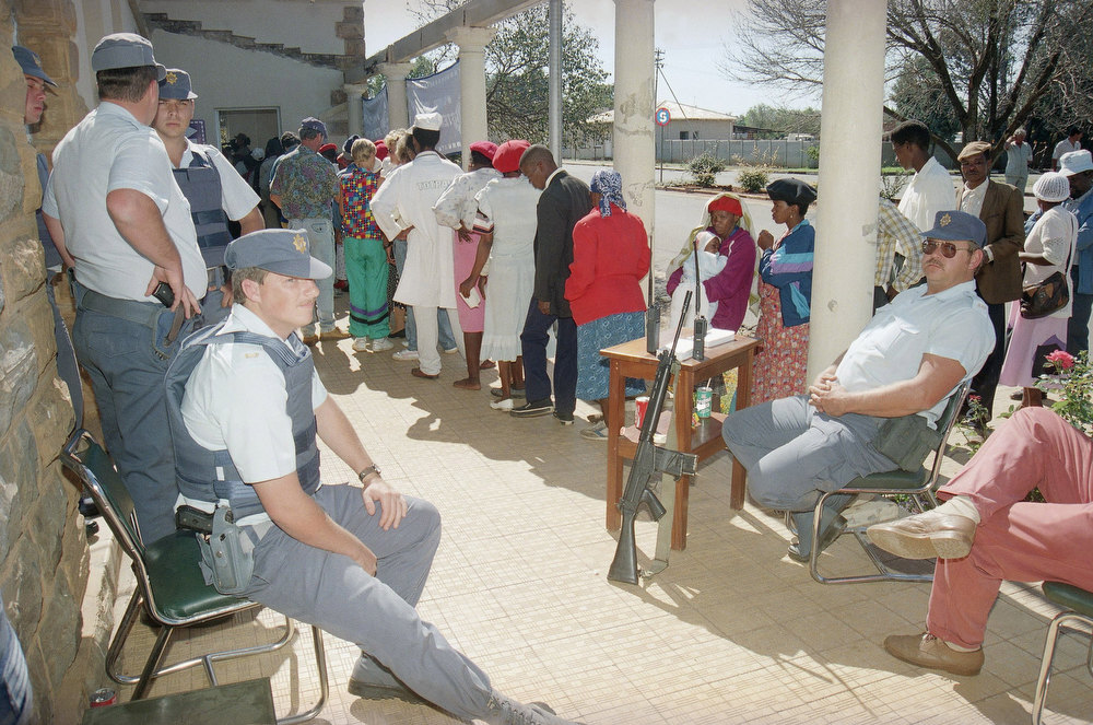 . South African Police provide security as voters line up to cast their ballot in Ventersdorp, South Africa, Wednesday, April 27, 1994, the heart of the ultra right wing territory. voters from all over the country are casting their ballot in the first ever all-race elections which expected to result in the naming of Nelson Mandela as the first black President. (AP Photo/Michael Yassukovich)