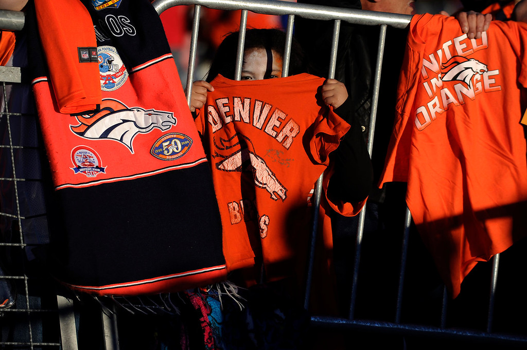 . Emily Gallegos, 8, of Pueblo, Colorado, holds up a Broncos shirt as she waits near the players exit after the AFC Championship game at Sports Authority Field at Mile High in Denver, Colorado on January 19, 2014. Broncos fans cheered on their team from sports bars around the city on Sunday. (Photo by Seth McConnell/The Denver Post)