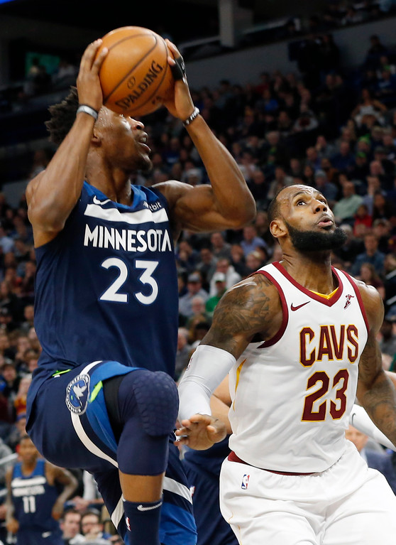 . Minnesota Timberwolves\' Jimmy Butler, left, eyes the basket along with Cleveland Cavaliers\' LeBron James in the first half of an NBA basketball game Monday, Jan. 8, 2018, in Minneapolis. (AP Photo/Jim Mone)