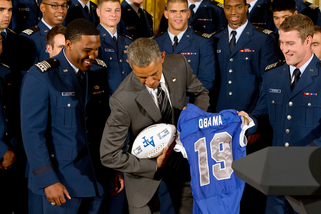 . Air Force defensive back Christian Spears, left, and quarterback Kale Pearson, right, smile as President Barack Obama poses with the football and jersey they gave him, during an event in the East Room of the White House in Washington, Thursday, May 7, 2015, where the president honored the U.S. Air Force Academy football team with the Commander-in-Chief Trophy. (AP Photo/Jacquelyn Martin)