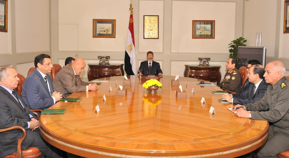 Description of . Egypt\'s President Mohamed Mursi (C) holds a meeting with his army chief and cabinet ministers at the presidential palace in Cairo December 6, 2012. Mursi met the army chief and cabinet ministers on Thursday to discuss how to stabilise the nation after clashes between his supporters and opponents outside the presidential palace, the presidency said in a statement. Mursi met General Abdel Fattah al-Sisi, who is the head of the military and defence minister, as well as the prime minister, interior and justice ministers, and others.  REUTERS/Egyptian Presidency/Handout