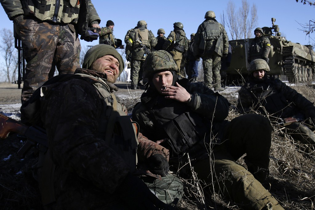 ". Ukrainian soldiers rest near Artemivsk after leaving the eastern Ukrainian city of Debaltseve in the Donetsk region on February 18, 2015. Ukrainian troops pulled out of the hotspot eastern town of Debaltseve after it was stormed by pro-Russian rebels in what the EU said was a ""clear violation\"" of an internationally-backed truce. ANATOLII STEPANOV/AFP/Getty Images"