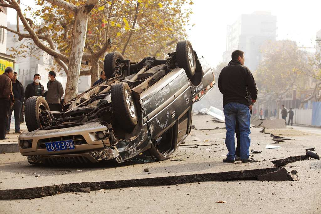 . A damaged vehicle lies along a street after an oil pipeline exploded, ripping roads apart, turning cars over and sending thick black smoke billowing over the city of Qingdao, east China\'s Shandong province on November 22, 2013, killing 35 people, authorities said, in the latest deadly industrial accident in the country.      AFP PHOTOSTR/AFP/Getty Images