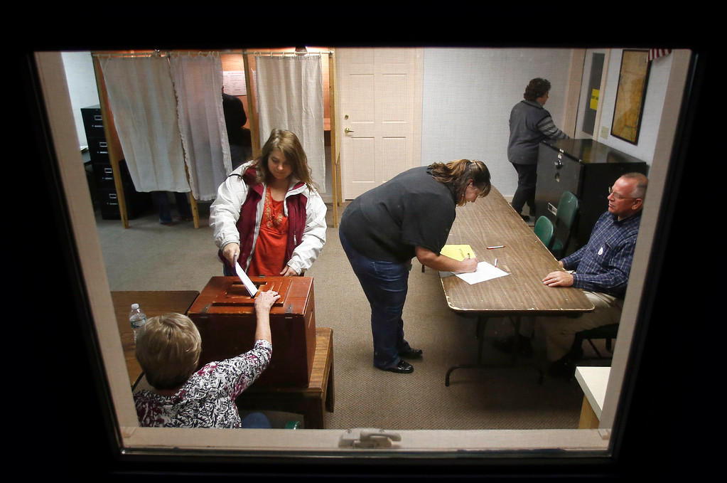 . Voters cast their ballots and sign petitions at the polling place in town hall in Knox, Maine, Tuesday, Nov. 4, 2014. (AP Photo/Robert F. Bukaty)