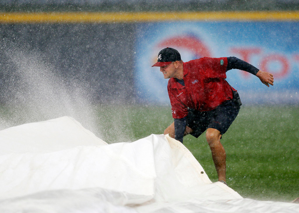 . A member of the Atlanta Braves grounds crew works to cover the infield during a rain delay. (AP Photo/John Bazemore)