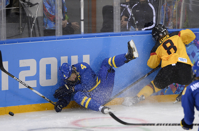 . Sweden\'s Jenni Asserholt falls after missing a hit on Germany\'s Julia Zorn (R) during the Women\'s Ice Hockey Group B match Germany vs Sweden at the Shayba Arena during the Sochi Winter Olympics on February 11, 2014. (JONATHAN NACKSTRAND/AFP/Getty Images)
