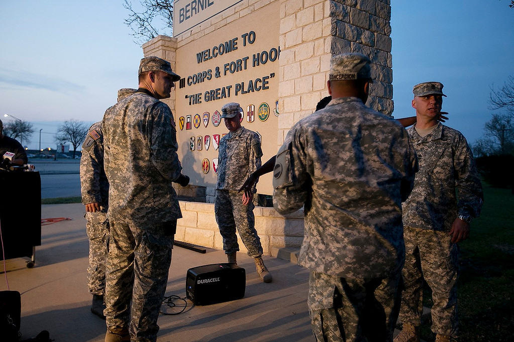 . Military personnel wait for a news conference to begin at Fort Hood, Texas, on Wednesday, April 2, 2014. A gunman opened fire in an attack that left four people killed including the shooter, at the same post where more than a dozen people were killed in a 2009 mass shooting, law enforcement officials said. The gunman died of a self-inflicted gunshot wound, officials said. At least 14 people were hurt in the shooting. (AP Photo/Austin American-Statesman, Deborah Cannon)