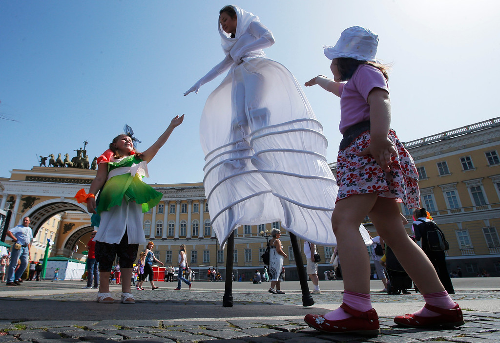 . Children play with an actor on stilts during a celebration marking the International Children\'s Day at Dvortsovaya (Palace) square in St.Petersburg, Russia, Saturday, June 1, 2013. (AP Photo/Dmitry Lovetsky)