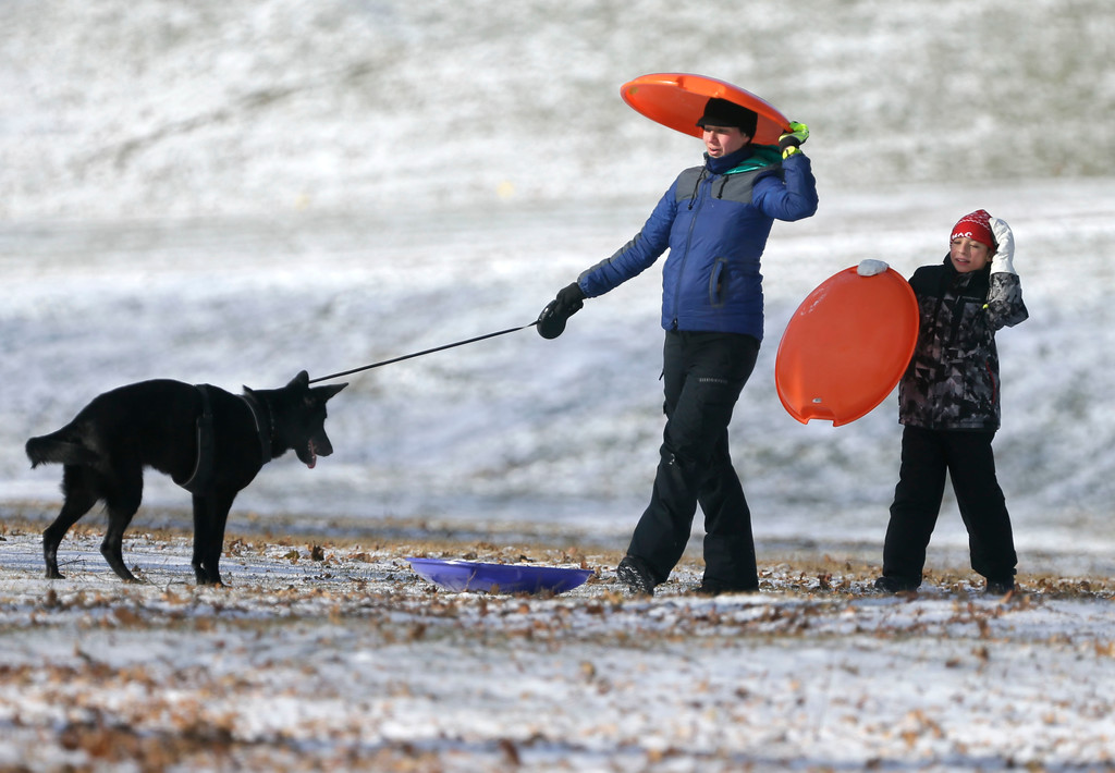 . Elizabeth Gallagher and Ian Fullmer, 10, Glendale, enjoy sledding and time with their dog Cocoa along Lake Front Drive as single digit bitter cold temperatures spread across southeast Wisconsin Tuesday, Dec. 26, 2017. (Rick Wood/Milwaukee Journal-Sentinel via AP)