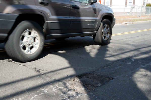 03/28/19 Wesley Bunnell | Staff A car drives past a pothole near 73 Ellis St in New Britain on Thursday afternoon. The pothole was reported by a resident using the See Click Fix app on March 26th with an acknowledgement by the city noting a referral to a streets foreperson.