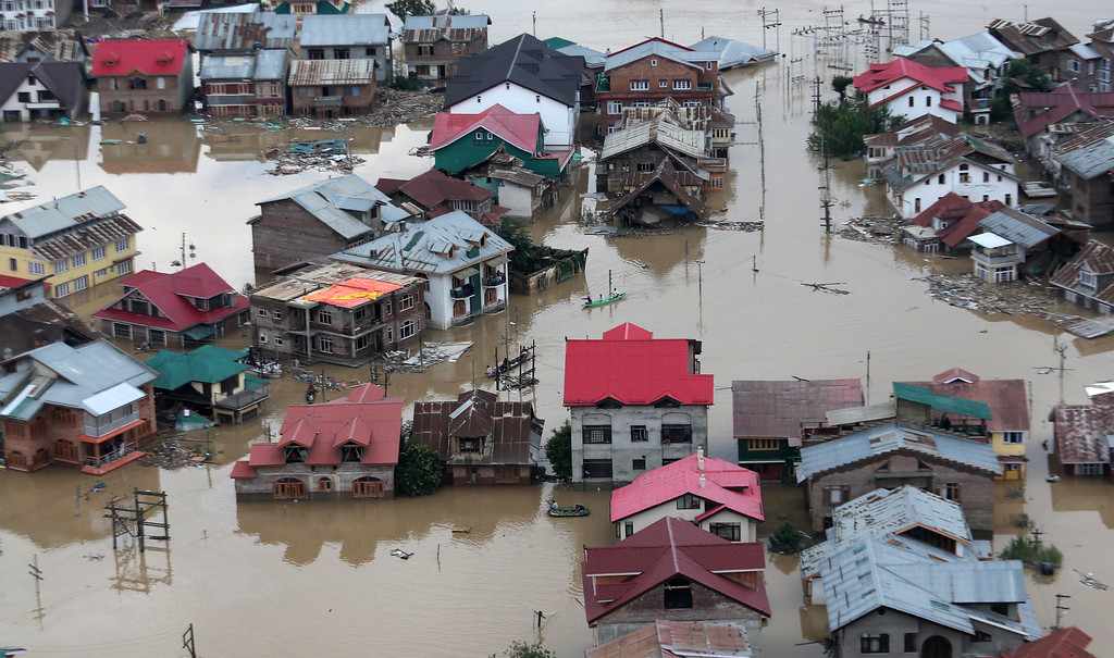 . Flood-affected people row boats past partially submerged buildings in floodwaters in Srinagar, India, Tuesday, Sept. 9, 2014.  (AP Photo/Dar Yasin)
