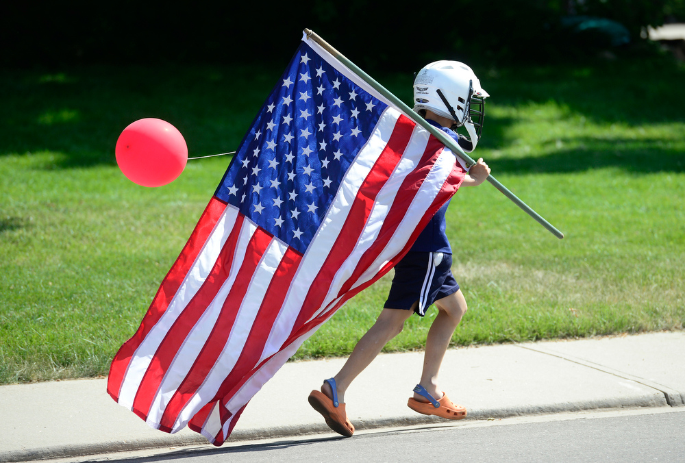 Description of . One participant tries to catch up to rest of the annual Fourth of July parade in The Greens neighborhood Friday morning, July 04, 2014. This was the 13th year for the parade according to organizer Jean Goldstein who participated in similar July Fourth celebrations organized by her father when she was growing up in Akron, Ohio.