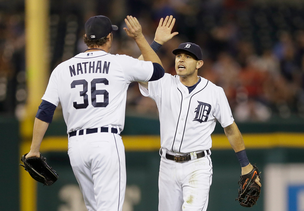 . Detroit Tigers relief pitcher Joe Nathan (36) and second baseman Ian Kinsler celebrate after catching Kansas City Royals pinch-runner Jarrod Dyson off second base during the ninth inning of a baseball game in Detroit, Tuesday, Sept. 9, 2014. Detroit won 4-2. (AP Photo/Carlos Osorio)
