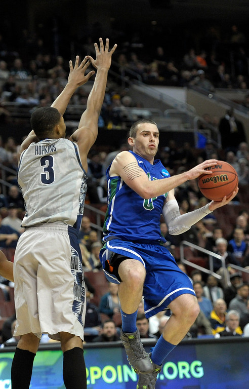 . Florida Gulf Coast\'s Brett Comer, right, looks to pass under pressure from Georgetown\'s Mikael Hopkins during the first half of a second-round game of the NCAA college basketball tournament, Friday, March 22, 2013, in Philadelphia. (AP Photo/Michael Perez)