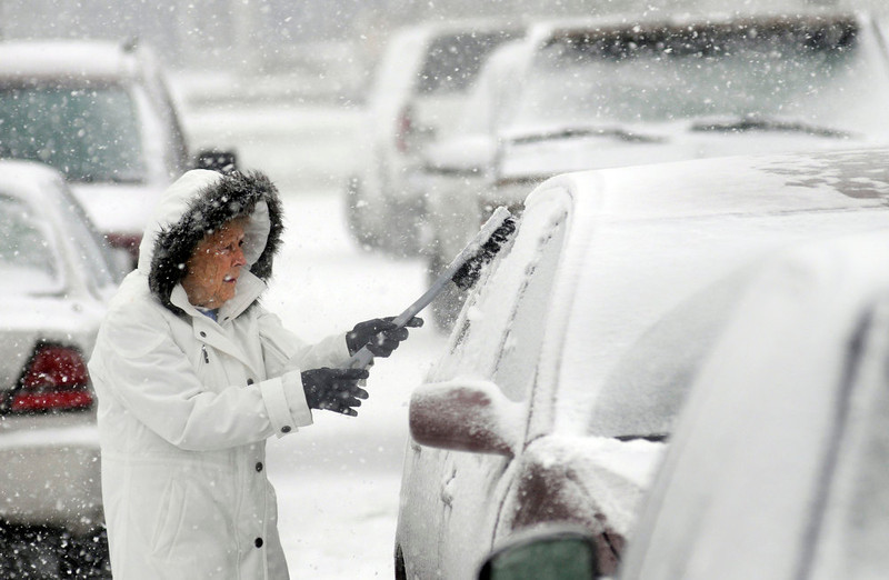 . Helen Earley cleans off her car in the parking lot of Hawkins Market in Ashland, Ohio Wednesday, Dec. 26, 2012 after buying groceries. (AP Photo/Ashland Times-Gazette, Tom E. Puskar)