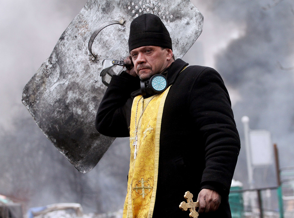 . A priest holds a cross and shield during clashes between anti-government protesters and riot police in central Kiev on February 20, 2014.   AFP PHOTO/ SERGEY GAPON/AFP/Getty Images