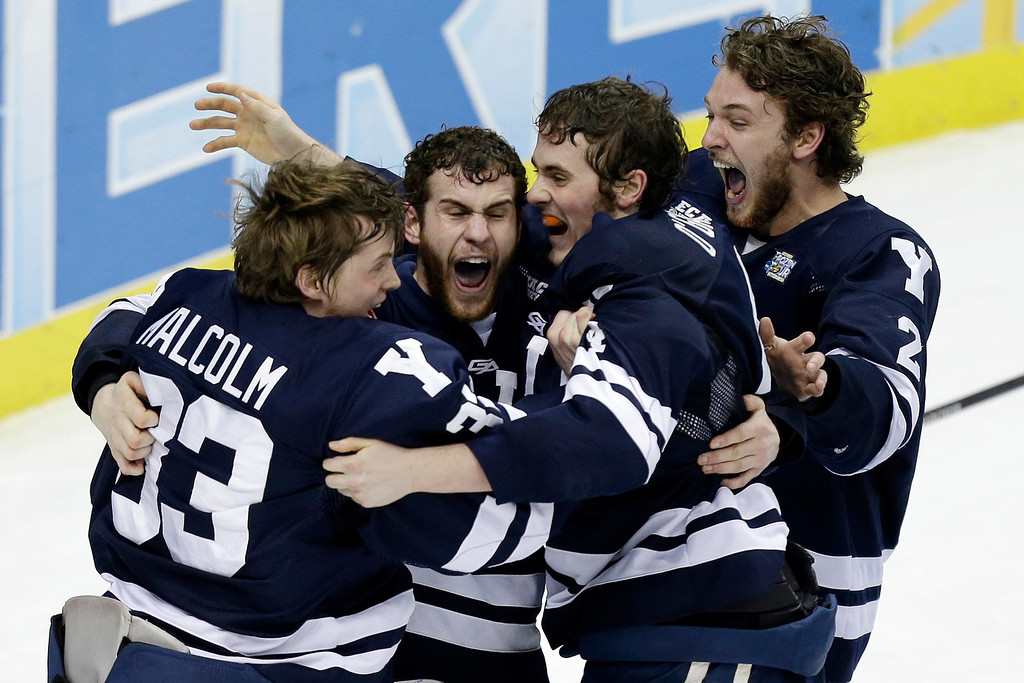 . Yale goalie Jeff Malcolm (33) is swarmed by teammates after shutting out Quinnipiac 4-0 to win the NCAA men\'s college hockey Frozen Four national championship game in Pittsburgh, Saturday, April 13, 2013.  (AP Photo/Gene Puskar)