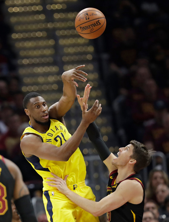. Indiana Pacers\' Thaddeus Young, left, passes over Cleveland Cavaliers\' Kyle Korver in the first half of Game 5 of an NBA basketball first-round playoff series, Wednesday, April 25, 2018, in Cleveland. (AP Photo/Tony Dejak)