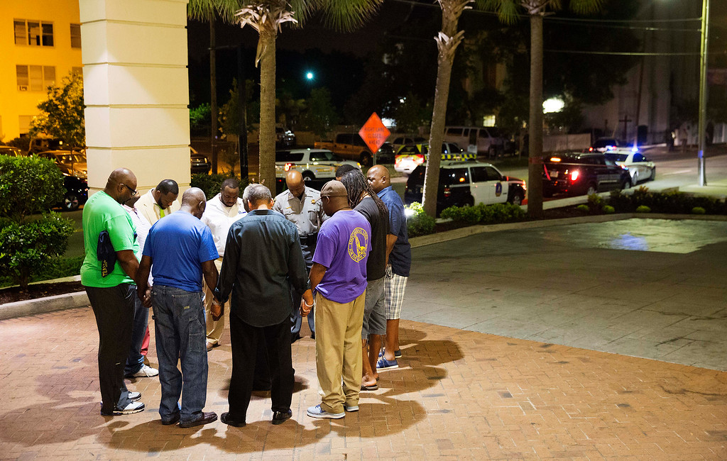 . Worshippers gather to pray in a hotel parking lot across the street from the scene of a shooting Wednesday, June 17, 2015, in Charleston, S.C. (AP Photo/David Goldman)