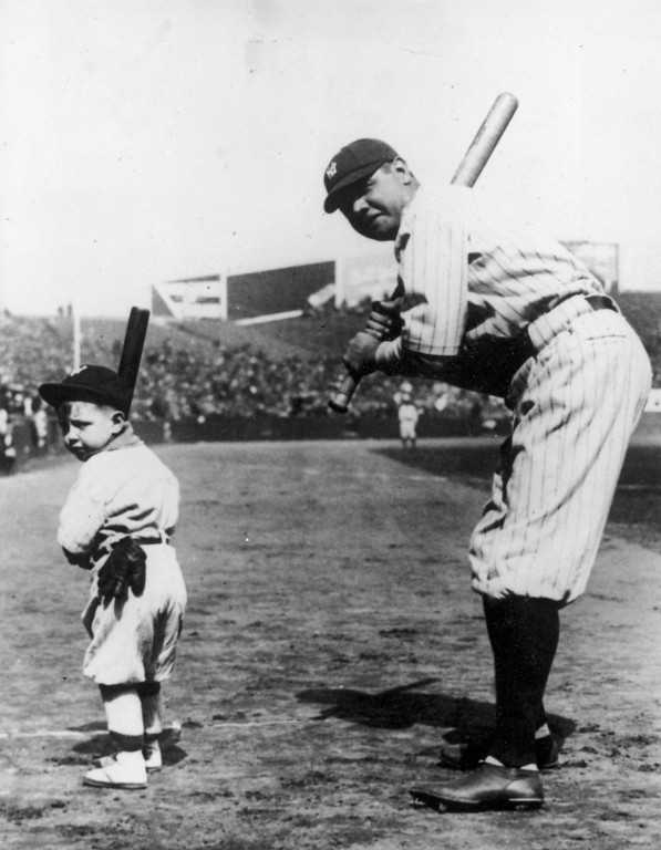 . 1933:  American baseball player, Babe Ruth (George Herman Ruth, 1895 - 1948) playing baseball in a full stadium with a small child.  (Photo by Central Press/Getty Images)
