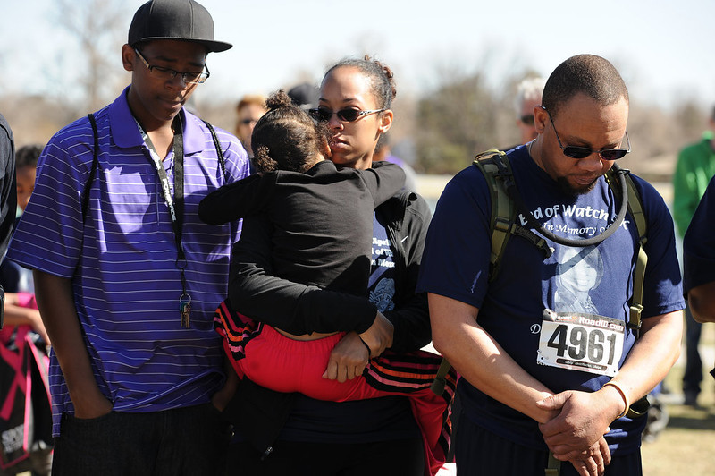 . Alancia  Unser, holds her daughter Sydney, 4, during a moment of silence at the  gathering for Celena Hollis after the race.  Her husband Joe Unser is a Sargent with the Denver Police Department. Family, colleagues, and friends of slain Denver Police Officer Celena Hollis turned out April 7, 2013 for a 5k run and walk to raise money for a scholarship fun and a memorial bench in City Park in Denver, CO.  Over 300 runners and walkers participated in the race that started at 9:00 am.  The race looped around City Park.  After the race, a gathering was held to remember Hollis and 22 white doves were released in her memory.  (Photo By Helen H. Richardson/ The Denver Post)