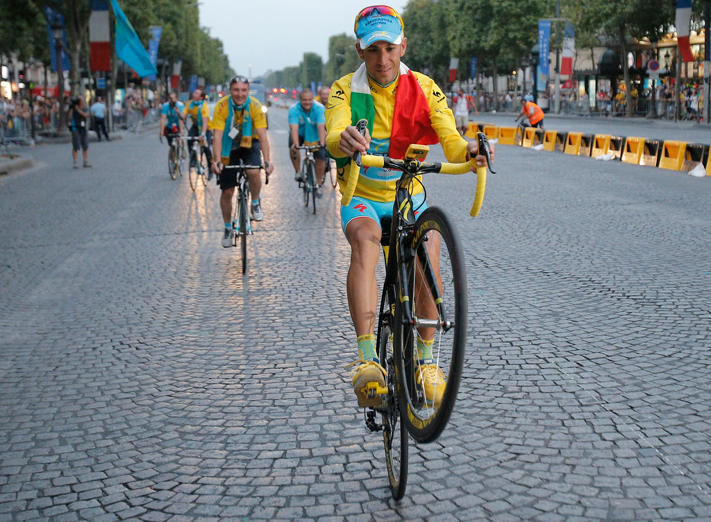 . 2014 Tour de France cycling race winner  Italy\'s Vincenzo Nibali pulls a wheelie during the team parade of the Tour de France cycling race in Paris, France, Sunday, July 27, 2014. (AP Photo/Christophe Ena)