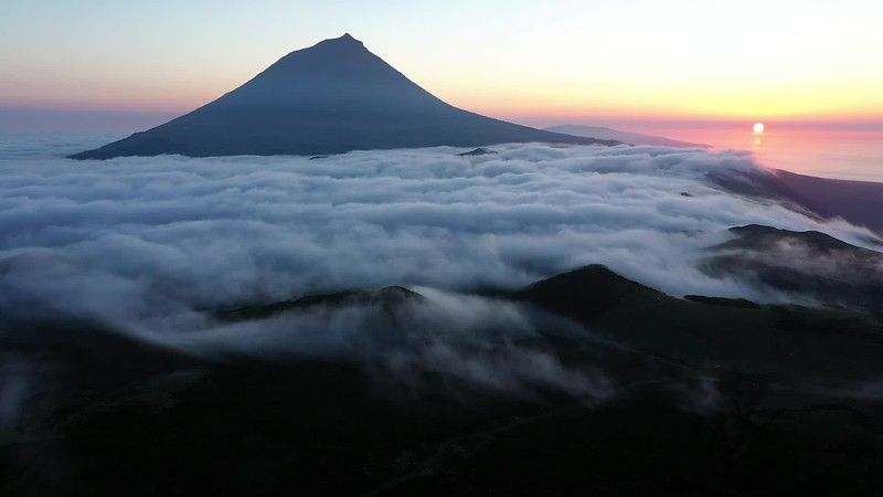 Available in 4K - Aerial image with magical sunset over a low cloud layer covering Pico Island, with the northcoast and Sao Jorge Island in the background, Azores