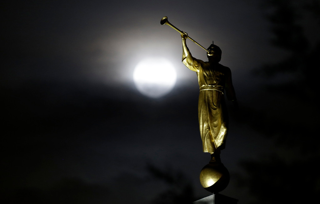 . The earth\'s shadow begins to fall on the moon during a total lunar eclipse, behind the Angel Moroni statue in Bogota, Colombia, early Wednesday, Oct. 8, 2014. (AP Photo/Fernando Vergara)