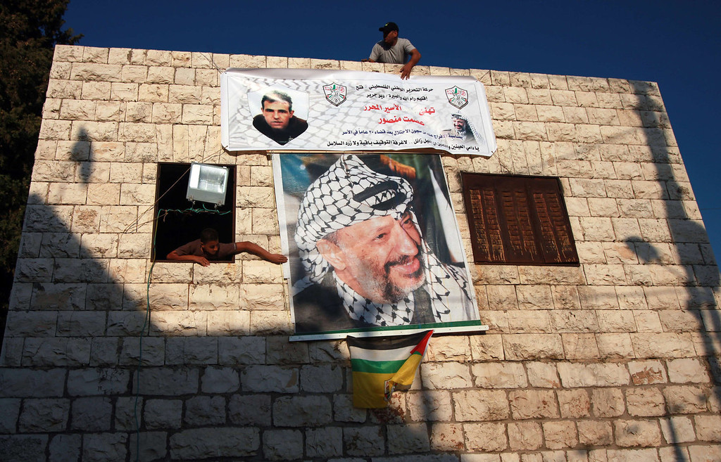 . Relatives of Esmat Mansour decorate his family\'s home with his pictures and a portrait of late Palestinian leader Yasser Arafat (bottom) in the West Bank village of Deir Jarir, near Ramallah, on August 13, 2013 in preparation to celebrate Mansour\'s arrival home. Mansour is one of 26 Palestinian prisoners, most of them held for deadly attacks, Israel has agreed to release this week as part of a deal brokered by the United States, which led to the resumption of negotiations in the Middle East.   ABBAS MOMANI/AFP/Getty Images