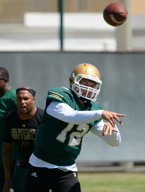 . Coach Antonio Pierce keeps a close eye on quarterback Josh Love during Long Beach Poly football practice Saturday, August 16, 2014, Long Beach, CA.   Photo by Steve McCrank/Daily Breeze