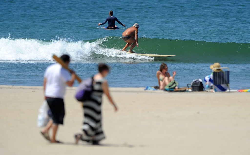. Despite the hot temperatures, the crowds at the beach were light in Seal Beach, CA on Tuesday, May 13, 2014. A surfer catches a small wave just north of the Seal Beach Pier. (Photo by Scott Varley, Daily Breeze)