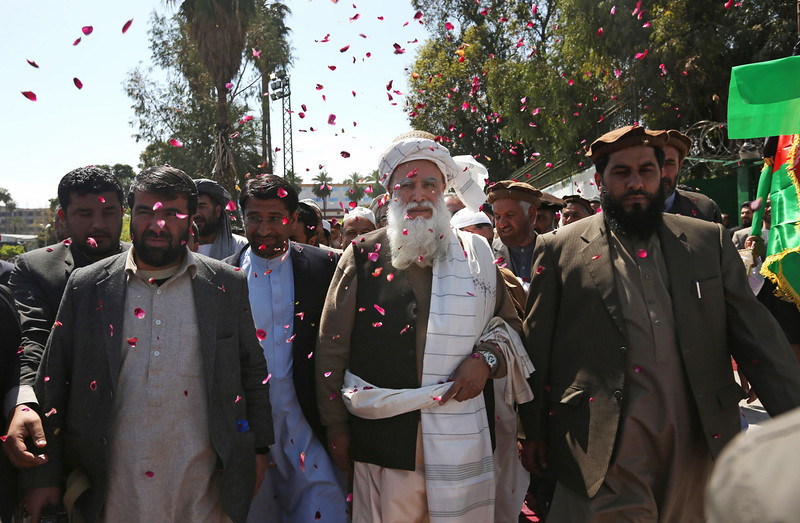 . Supporters of Afghan presidential candidate Abdul Rasoul Sayyaf, center, throw confetti towards him as they welcome him during a campaign rally in Jalalabad, east of Kabul, Afghanistan, Tuesday, April 1, 2014. Eight Afghan presidential candidates are campaigning for the third presidential election. Elections will take place on April 5, 2014. (AP Photo/Rahmat Gul)