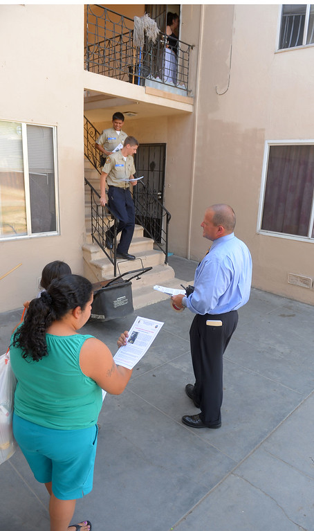 """. Long Beach detectives and search and rescue volunteers hand out fliers in a neighborhood surrounding 7th Street and Orange Avenue in Long Beach, CA on Tuesday, May 13, 2014. The LBPD is looking for witnesses or anyone with knowledge of the March 24 shooting at the Cerritos Mini Market which left owner Felix Avela in critical condition after being shot during a robbery. The suspect is described as a black male in his late teens or early 20\'s with an average build and wearing a black hoodie sweatshirt with the word \""""Cali\"""" on the front. Anyone with info is asked to call LBPD at 562-570-7464 or 800-222-TIPS. (Photo by Scott Varley, Daily Breeze)"""