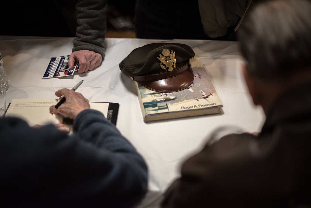 """. 03/26/17 LEOMINSTER with story-- World War II veteran Vincent \""""Bill\"""" Purple has his hat on a a book called \""""The Mighty Eighth\"""" during Sunday\'s book signing at the Veterans Center in Leominster of \""""My Father\'s War\"""" written by local author Charley Valera.  (Sentinel & Enterpirse photo/Jeff Porter)"""