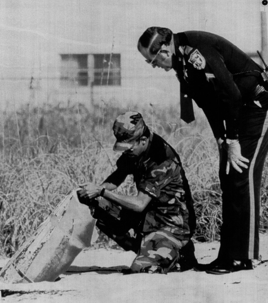 Description of . The military and a county sheriff examine debris thought to be from the space shuttle Challenger found off Cocoa Beach on Jan. 29, 1986.  Denver Post Library Archive