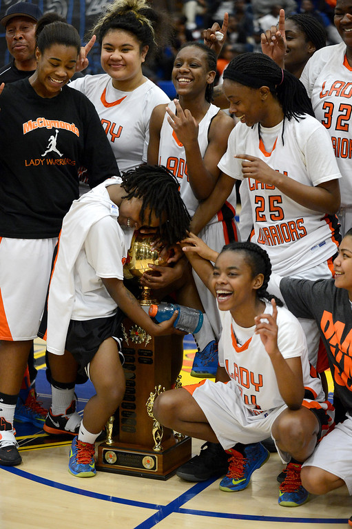 . McClymonds High\'s Gabby Gaines (1), left, hugs the trophy following their win over Oakland Tech High in their Oakland Section high school girls basketball championship game played at Merritt College in Oakland, Calif. on Thursday, Feb. 28, 2013. (Dan Honda/Staff)