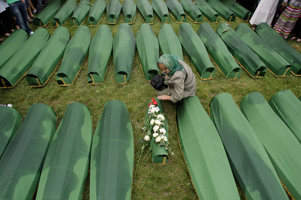 . A Bosnian woman says prayers next to the coffin of a child during a funeral ceremony at the memorial center in Potocari, near Srebrenica, 160 kms east of Sarajevo, Bosnia, Thursday, July 11, 2013. People from around Bosnia and abroad have begun arriving in Srebrenica to commemorate the 18th anniversary of the 1995 massacre and rebury recently identified victims exhumed from mass graves. The victims\' bodies are still being exhumed from mass graves in the area, where Serbs had dumped them in an attempt to cover up the crime. Identified victims are buried each year on the massacre\'s anniversary at a memorial cemetery near Srebrenica. (AP Photo/Amel Emric)
