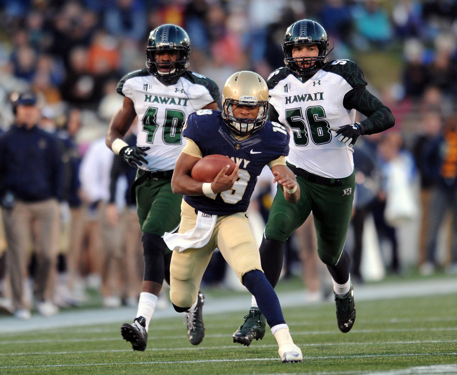 . Navy\'s quarterback Keenan Reynolds, center, runs the ball as Hawaii\'s Jerrol Garcia-Williams, left, and Brenden Daley purue in the first half of an NCAA college football game on Saturday, Nov. 9, 2013, in Annapolis, Md. (AP Photo/Gail Burton)