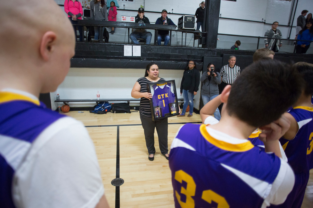Head coach Luis Pineda, at Christ the King, hugs Angela Rodriguez (Vinny's mom) while her daughter, Selena Valdivieso looks on. Coach is holding a framed jersey of Vinny's. <br /> Here, Vinny's mom wished the team well in their final(?) game.<br /> Coach can be contacted at 913-787-1977 or Chumlee82@gmail.com