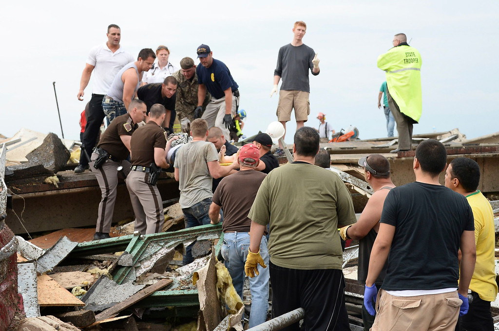 . Rescue workers help free one of the 15 people that were trapped at a medical building at the Moore hospital complex after a tornado tore through the area of Moore, Oklahoma May 20, 2013. REUTERS/Gene Blevins
