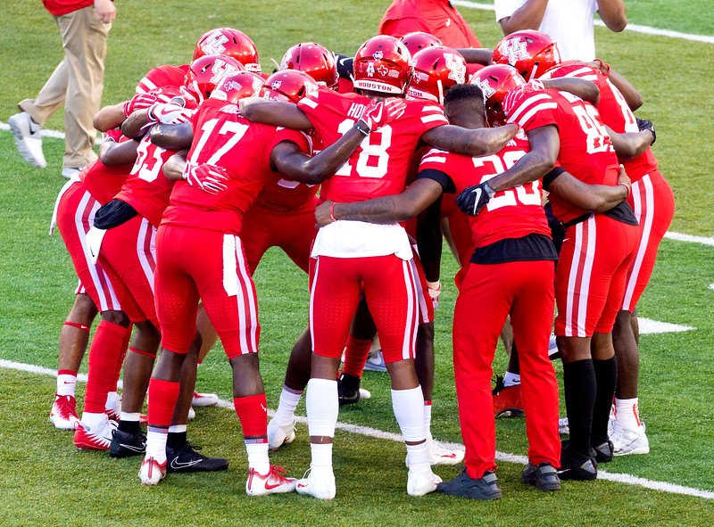 The UH starting offense huddle during their warmups.