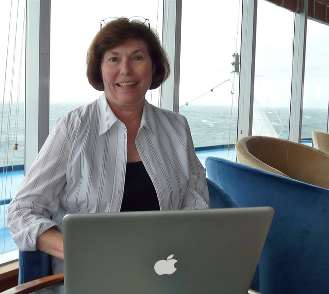 A woman sits in an observation lounge of a ship using her laptop.