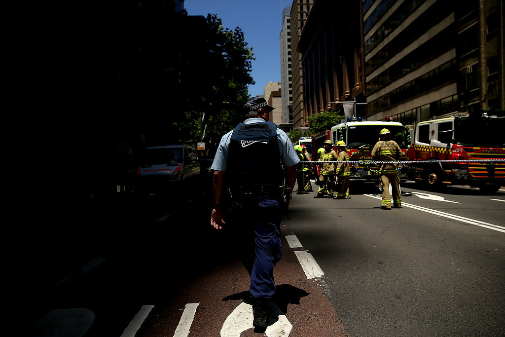 . SYDNEY, AUSTRALIA - DECEMBER 15:  A policeman and Firemen are seen at a barricade on Castlereigh Street on December 15, 2014 in Sydney, Australia.  Police attend a hostage situation at Lindt Cafe in Martin Place.  (Photo by Mark Metcalfe/Getty Images)