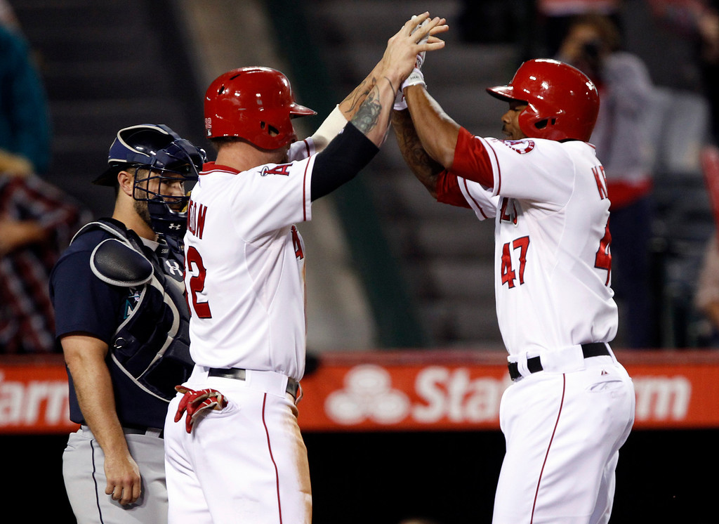 . Los Angeles Angels\' Josh Hamilton, left, congratulates Angels\' Howie Kendrick (47) for hitting a two-run home run against the Seattle Mariners in the fourth inning during a baseball game Tuesday, May 21, 2013 in Anaheim. Seattle Mariners catcher Kelly Shoppach, left, looks on to make sure Kendrick tags home plate.   (AP Photo/Alex Gallardo)