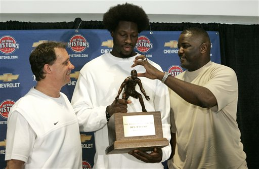 Description of . Joe Dumars, Detroit Pistons president of basketball operations, right, gestures that an afro is missing from the trophy as Pistons center Ben Wallace holds his 2006 NBA Defensive Player of the Year award while head coach Flip Saunders, left, looks on in Auburn Hills, Mich., Monday, May 8, 2006. This marks the fourth time in five years that Wallace has won the basketball defensive award. (AP Photo/Paul Sancya)