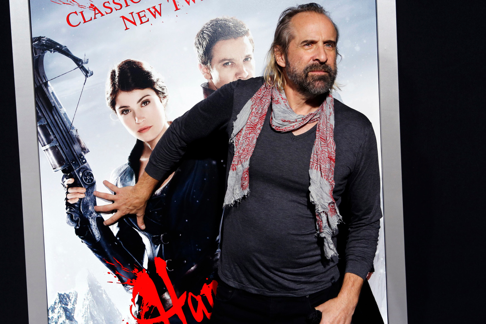 ". Actor Peter Stormare gropes a poster of Gemma Arterton as he arrives at the premiere of the film ""Hansel and Gretel: Witch Hunters\"" at Grauman\'s Chinese Theatre in Hollywood, California January 24, 2013. REUTERS/Patrick Fallon"