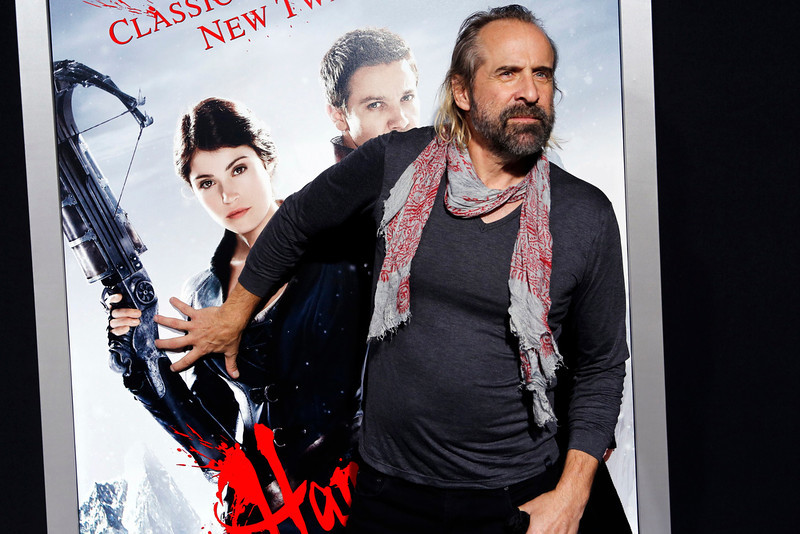 """. Actor Peter Stormare gropes a poster of Gemma Arterton as he arrives at the premiere of the film \""""Hansel and Gretel: Witch Hunters\"""" at Grauman\'s Chinese Theatre in Hollywood, California January 24, 2013. REUTERS/Patrick Fallon"""