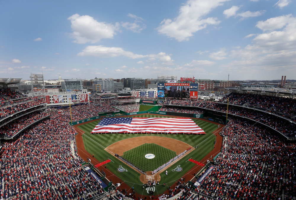 . Members of the Miami Marlins and Washington Nationals listen to the national anthem prior to the start of their opening day game at Nationals Park on April 1, 2013 in Washington, DC.  (Photo by Rob Carr/Getty Images)