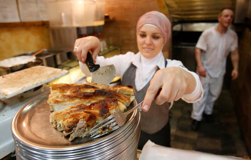 ". In this Tuesday, May 6, 2014 photo, a woman serves up a local dish of meat pie in Sarajevo, Bosnia-Herzegovina. Despite the dark chapters of the past, today the city is defined by what locals call ""the Sarajevo Spirit\"", an interesting and mostly harmonious mix of religions and cultures. (AP Photo/Amel Emric)"