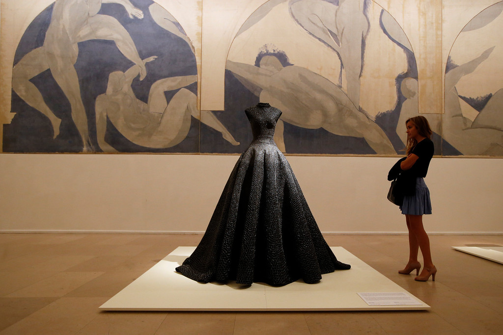 """. A visitor, Una Duval age 21, looks at \""""Long Dress\"""" of woven raffia, silver thread and bead embroidery of Spring Summer 1997 collections by French Tunisian born Fashion designer Azzedine Alaia, presented for the first Paris retrospective of couturier front of \""""Lutte des Nymphes\"""", 1931 by Matisse at the Museum of Modern Art in Paris, Wednesday, Sept. 25, 2013. A selection of seventy iconic models retracing a unique creative career of Alaia are displayed for the reopening of the Galliera Museum and in the Matisse room at the Museum of Modern Art of Paris. (AP Photo/Francois Mori)"""